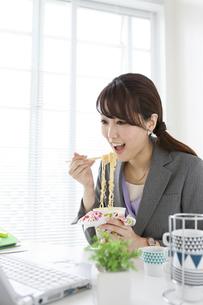 カップラーメンを食べるビジネスウーマンの写真素材 [FYI01307710]