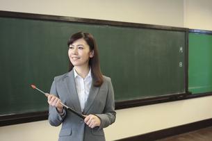 黒板の前に立つ女性教師の写真素材 [FYI01307777]