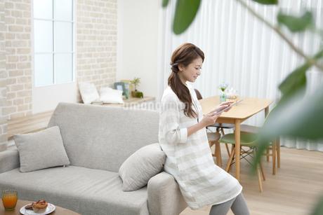 タブレットPCを操作する女性の写真素材 [FYI01308089]
