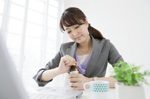 栄養ドリンクを持つビジネスウーマンの写真素材 [FYI01308457]