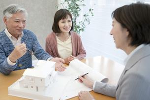 ビジネスウーマンの説明を聞くシニア夫婦の写真素材 [FYI01308503]