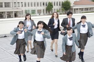屋上を走る女子校生と先生の写真素材 [FYI01308589]