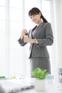 栄養ドリンクを持つビジネスウーマンの写真素材 [FYI01308639]
