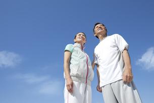 青空とスポーツウェアを着たシニア夫婦の写真素材 [FYI01308660]