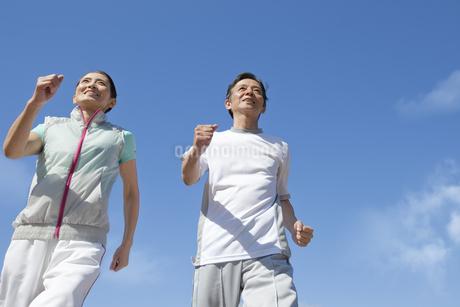青空とジョギングをするシニア夫婦の写真素材 [FYI01308747]