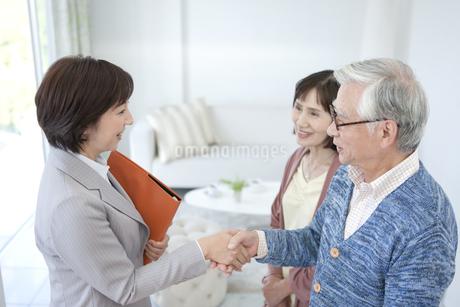 握手をするビジネスウーマンとシニア夫婦の写真素材 [FYI01308765]