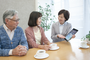 ビジネスウーマンの説明を聞くシニア夫婦の写真素材 [FYI01308787]