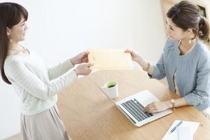 書類の受け渡しをする女性2人の写真素材 [FYI01308845]