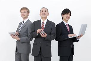 端末を操作するビジネスマン3人の写真素材 [FYI01308877]