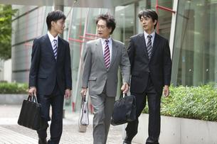 話をしながら歩くビジネスマン3人の写真素材 [FYI01308936]