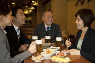 居酒屋で話をするビジネスマン4人の写真素材 [FYI01309036]