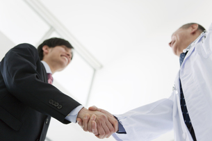 握手をするビジネスマンと医師の写真素材 [FYI01309103]