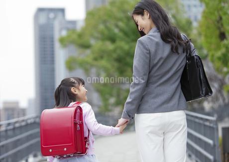 手をつないで歩く女の子と母親の後姿の写真素材 [FYI01309104]