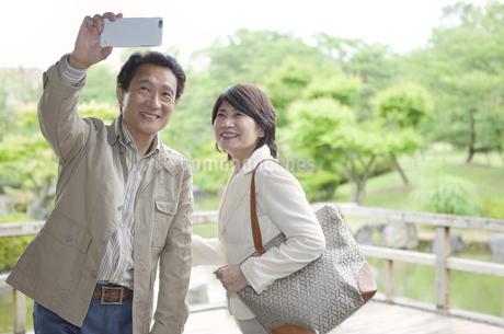 写真を撮る中高年夫婦の写真素材 [FYI01309143]