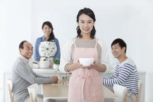 皿を持つ女性と家族の写真素材 [FYI01309200]