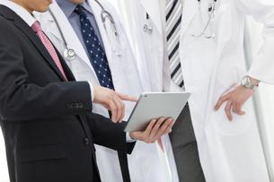 医師にタブレットPCを見せるビジネスマンの手元の写真素材 [FYI01309233]