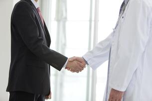 握手をするビジネスマンと医師の手元の写真素材 [FYI01309303]