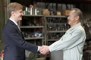握手するビジネスマンと作業者の写真素材 [FYI01309351]
