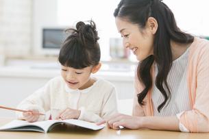 娘の勉強を見る母親の写真素材 [FYI01309402]