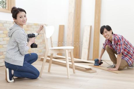 椅子を組み立てる夫婦の写真素材 [FYI01309418]