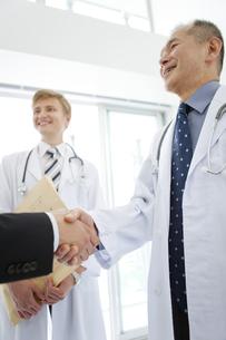 握手をする医師とビジネスマンの手元の写真素材 [FYI01309471]