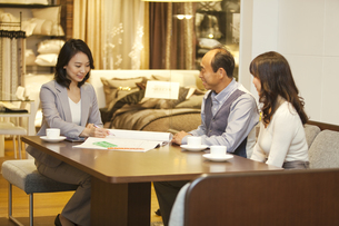 ビジネスウーマンと話す中高年夫婦の写真素材 [FYI01309478]