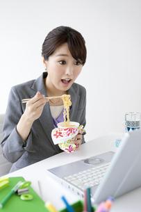 カップラーメンを食べるビジネスウーマンの写真素材 [FYI01309488]