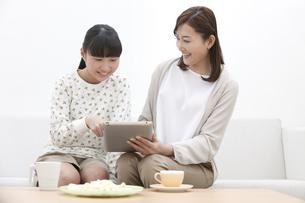タブレットPCを見て話す親子の写真素材 [FYI01309505]