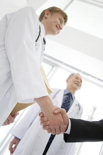 握手をする医師とビジネスマンの手元の写真素材 [FYI01309544]
