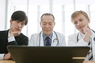 ノートパソコンを見るビジネスマンと医師3人の写真素材 [FYI01309608]