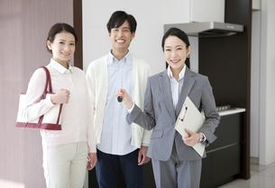 鍵を持つビジネスウーマンと笑顔の夫婦の写真素材 [FYI01309710]