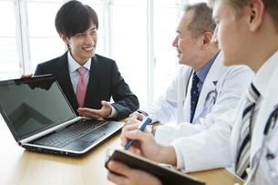 医師にノートパソコンを見せるビジネスマンの写真素材 [FYI01309727]
