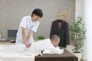 横になってマッサージを受けるシニア男性の写真素材 [FYI01309753]