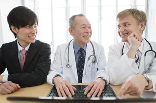 ノートパソコンを操作する医師とビジネスマン3人の写真素材 [FYI01309806]