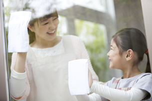 窓拭きをする女の子と母親の写真素材 [FYI01309815]