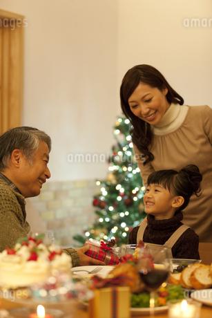 クリスマスプレゼントを渡す3世代家族3人の写真素材 [FYI01309826]