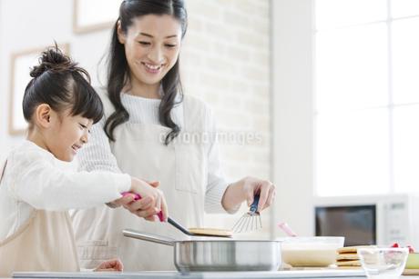料理をする女の子と母親の写真素材 [FYI01309828]