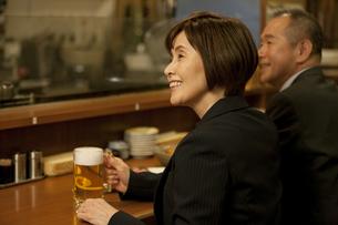 居酒屋のカウンターに座るビジネスウーマンとビジネスマンの写真素材 [FYI01309831]