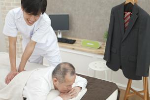 マッサージを受けるシニア男性とマッサージ師の写真素材 [FYI01309879]