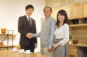 ビジネスマンと握手をする中高年夫婦の写真素材 [FYI01309902]