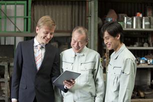 タブレットPCを見るビジネスマンと作業者2人の写真素材 [FYI01309941]
