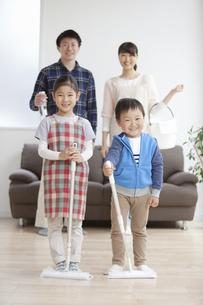 掃除道具を持つ家族4人の写真素材 [FYI01310006]