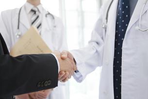 握手をする医師とビジネスマンの手元の写真素材 [FYI01310024]