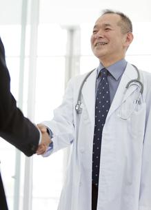 握手をするビジネスマンと医師の写真素材 [FYI01310221]