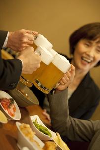 ビールで乾杯するビジネスマン4人の手元の写真素材 [FYI01310227]