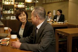 居酒屋で話をするビジネスマンとビジネスウーマンの写真素材 [FYI01310237]