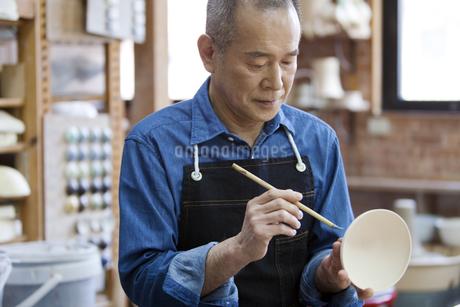 茶碗に絵を描くシニア男性の写真素材 [FYI01310254]