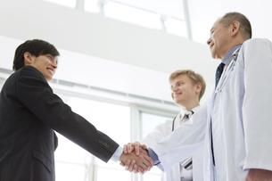 握手をする医師とビジネスマンの写真素材 [FYI01310301]