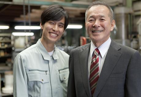 笑顔のビジネスマンと作業者の写真素材 [FYI01310321]