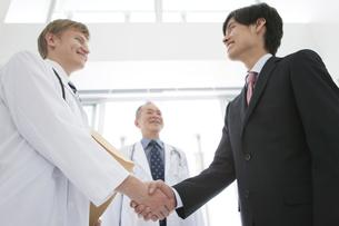 握手をする医師とビジネスマンの写真素材 [FYI01310381]